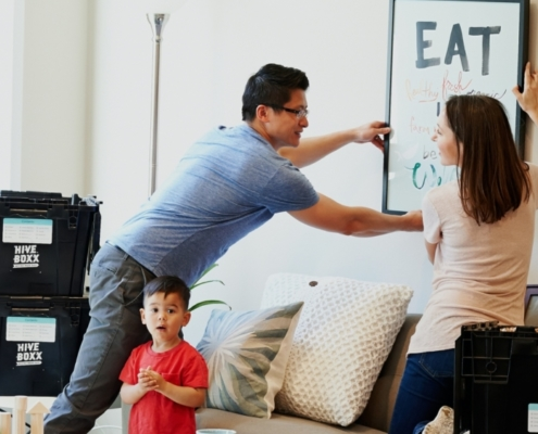 Mom, dad, and child in the middle of moving into a new home